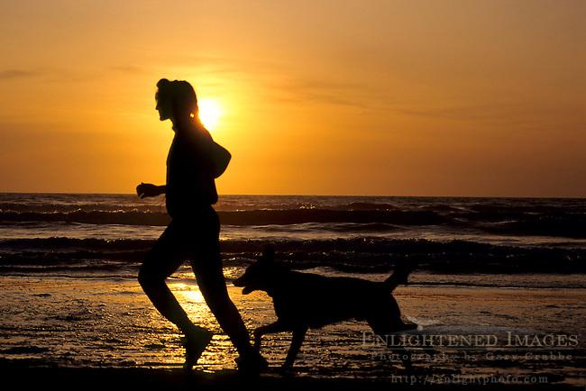 Woman and pet dog running on beach at sunset, near Samoa, Humboldt County, California