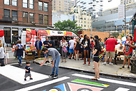 View of the crowd at the block party with the food truck in the background.