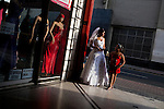 A woman in a wedding dress watches the street on Sunday, Apr. 12, 2009 in Lima, Peru.