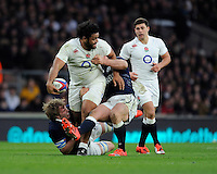 Billy Vunipola of England looks to offload as he is tackled by Jonny Gray of Scotland