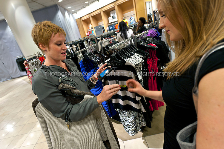 7/8/2011--Seattle, WA, USA..Danielle Wood(left), a salesperson at Nordstrom's downtown Seattle store, rings up a sale using a mobile device with a customer, Rachel Canning (right) by swiping a credit card through a reader attached to an iPod Touch. Clerks at Nordstrom walk around with mobile devices ( iPod Touch) and check out customers wherever they're sitting or standing, sending e-receipts...©2011 Stuart Isett. All rights reserved.