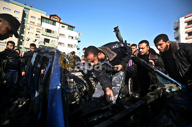 Palestinain policemen inspect the remains of a vehicle after it exploded in Gaza City March 9, 2012. Israel killed the leader of a Palestinian militant faction on Friday in a targeted attack on the car in the Gaza Strip, an Israeli official said. A second man also died in the blast, and a third was injured. The attack came shortly after two rockets were fired at Israel from the coastal territory, causing no damage or injury.Photo by  Ali Jadallah