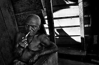 An old man smokes pipe on the porch of his wooden house in the poor neigbourhood of Tumaco, Colombia, 11 June 2010.