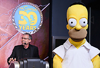 """New York - DECEMBER 17: Mike Scully speaks to the media as he participates in the ceremonial lighting of the Empire State Building as they attend the Empire State Building Celebration of the 30th Anniversary of FOX's """"The Simpsons"""" on December 17, 2018 in New York City.  (Photo by Anthony Behar/FOX/PictureGroup)"""
