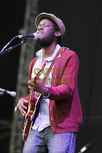 Michael Kiwanuka.Performing live at Hard Rock Calling, Hyde Park London, England, UK, .June 24th 2011..music festival concert gig on stage half length playing guitar red cardigan jeans blue white cap hat  jacket microphone singing .CAP/MAR.© Martin Harris/Capital Pictures.