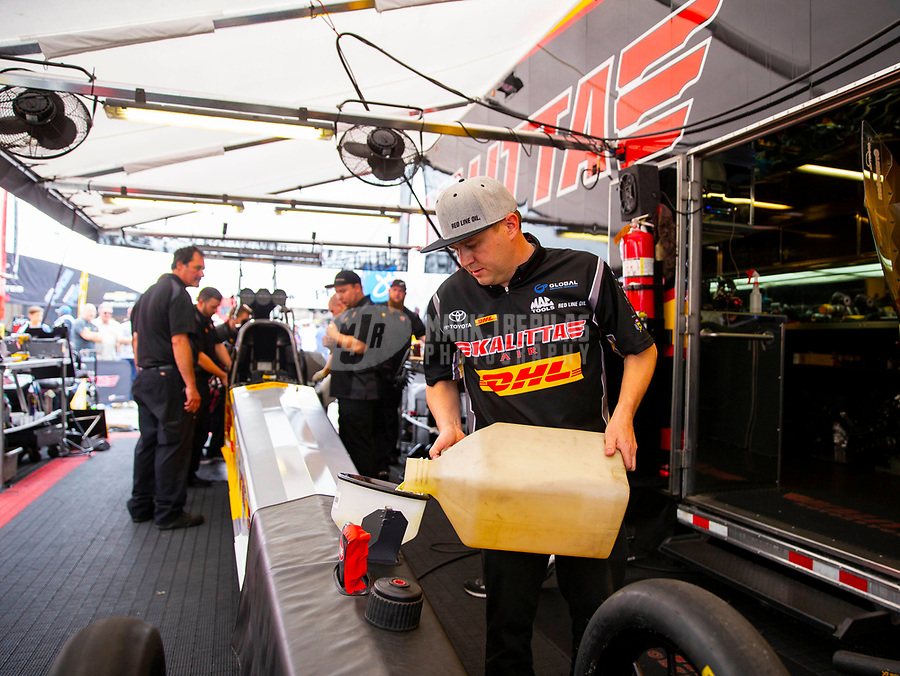 May 5, 2018; Commerce, GA, USA; NHRA top fuel driver Richie Crampton pours nitro methane race fuel into the gas tank of his dragster in the pits during qualifying for the Southern Nationals at Atlanta Dragway. Mandatory Credit: Mark J. Rebilas-USA TODAY Sports