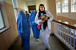 Accompanied by two female hospital staff members, ICRC nurse Kristina Alho of Jyvaskyla, Finland, carries a baby girl through hallways to see her mother in the women's intensive care unit at Mirwais Hospital in Kandahar, Afghanistan, April 23, 2009. The child was delivered by Caesarian section. Afghanistan has one of the highest rates of infant mortality in the world. Despite worsening security, development continues at Mirwais Hosptial, where the International Committe of the Red Cross conducts training and assists the local staff. Mirwais is the main public hosptial serving five southern provinces. As security has deteriorated in the South, many international NGO's have pulled their staff from the area or shut down the regional office, stunting development in a region where it is badly needed.