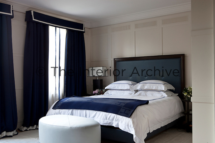 The wood panelled bedroom has a blue and white colour scheme and a blue leather bed