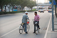 Daytime landscape view of two men on bicycles talking while stopped on the Chao Yang Lu in Cháoyáng Q? in Beijing.  © LAN
