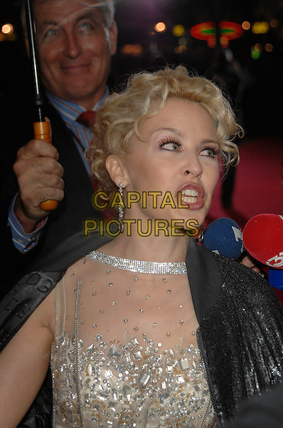 "KYLIE MINOGUE.Attending the ""White Diamond"" UK film premiere Vue West End cinema, Leicester Square, London, England, .16th October 2007. .portrait headshot earrings black coat jacket funny face mouth.Ref: CAP/PL.©Phil Loftus/Capital Pictures"
