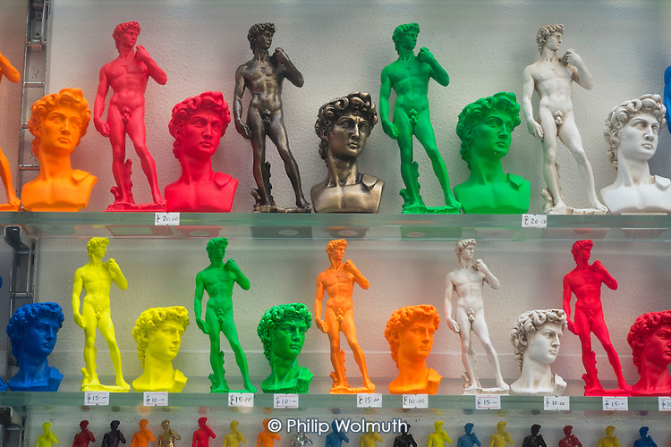 Multicoloured models of Michelangelo's David. Souvenir shop window, Florence , Italy