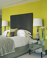 In this elegant bedroom an over-sized black headboard is used in stunning contrast to the acid yellow wall behind