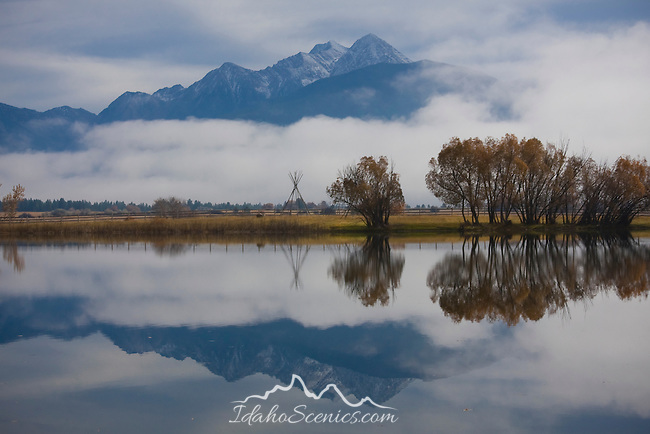 Montana, Western, St. Ignatious. Calm waters reflect the snowcapped Mission Mountains in autumn.