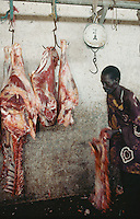 Gambia. Banjul. Banjul is the capital of the republic of  Gambia.  Meat market. A black worker carries a piece of a dead animal's fresh red meat .© 2000 Didier Ruef