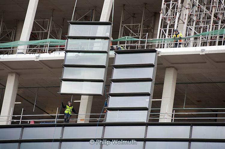 A steel and glass panel is lowered into place by a crane on the Francis Crick Institute, Kings Cross.