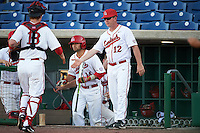Ball State Cardinals coach Scott French (12) greets catcher <br /> Griffin Hulecki (13) in between innings with Maverick Bacon (14) coming out of the dugout to hit during a game against the Louisville Cardinals on February 19, 2017 at Spectrum Field in Clearwater, Florida.  Louisville defeated Ball State 10-4.  (Mike Janes/Four Seam Images)