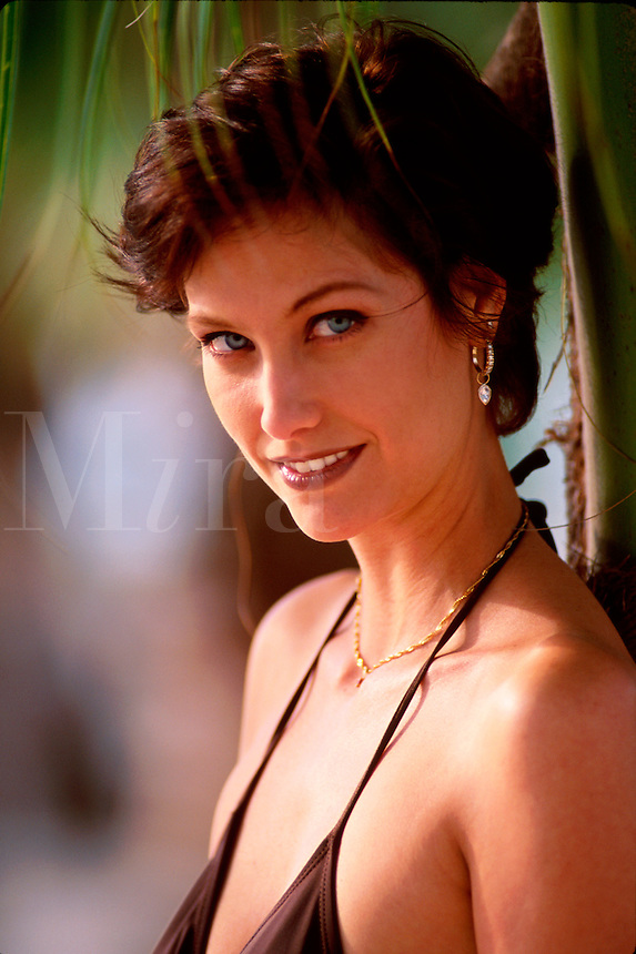 Portrait of a smiling female model with blue-green eyes as she poses under a palm tree.