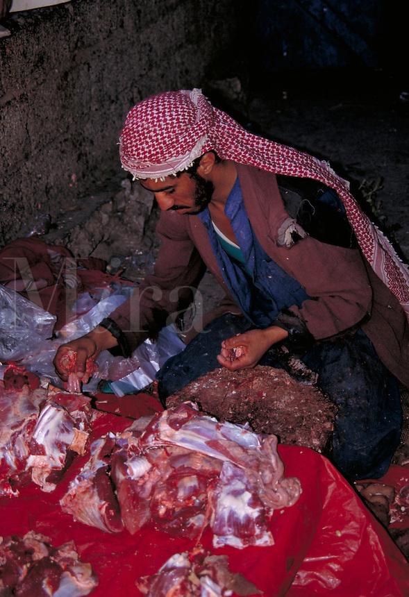 A butcher at a street market in Yemen sorts the cuts of meat he sells. Yemen.