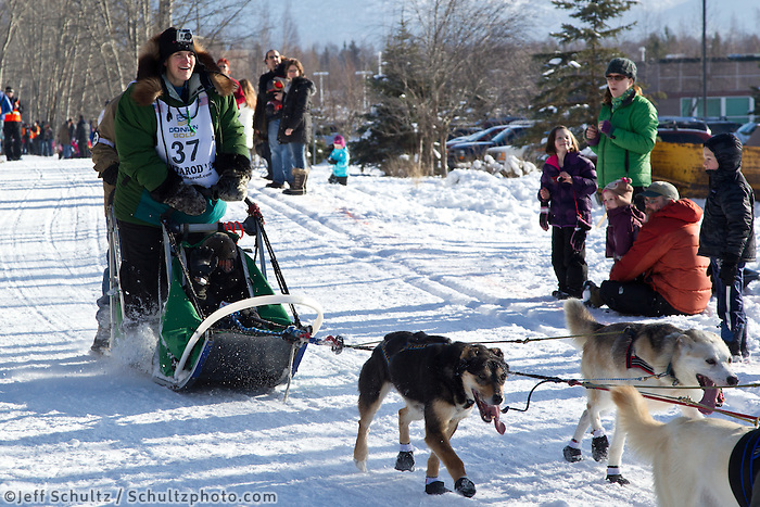 Christine Roalofs and team run past spectators on the bike/ski trail during the Anchorage ceremonial start during the 2013 Iditarod race.    Photo by Britt Coon/IditarodPhotos.com