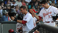Outfielder Drew Turocy (28), left, and Garin Cecchini (17) of the Greenville Drive are congratulated after scoring a run in a game against the Charleston RiverDogs on June 2, 2012, at Fluor Field at the West End in Greenville, South Carolina. Greenville won, 10-4. (Tom Priddy/Four Seam Images)