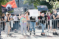 "Counterprotesters hold signs toward, flip-off, and angrily shout at those marching in the Straight Pride Parade in Boston, Massachusetts, on Sat., August 31, 2019. The parade was organized in reaction to LGBTQ Pride month activities by an organization called Super Happy Fun America. The people's signs here read ""Nazis make my soul cry"" and ""You lost twice / Get Over It!"""
