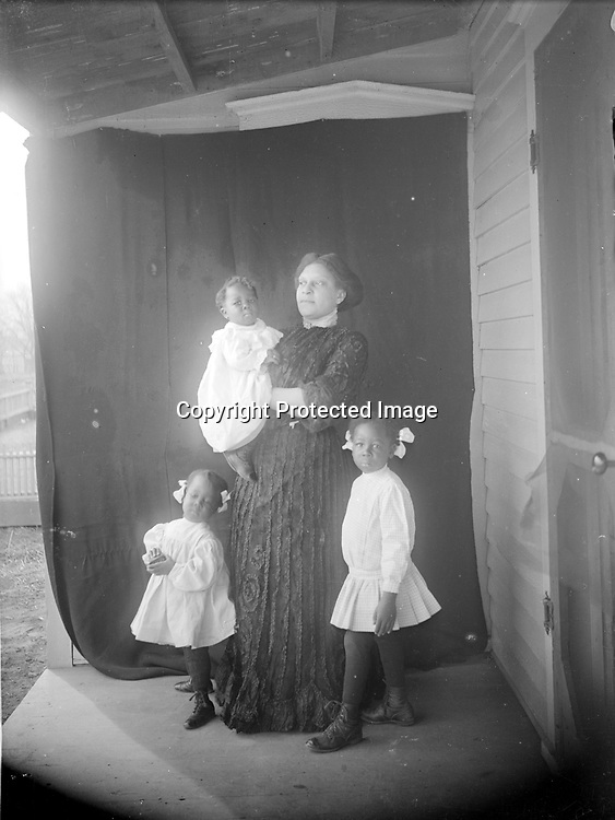 Note: also see image LB074 this image is FLIPPED!<br /> MATRON AND CHILDREN. Hopefully, someday a descendant of this family will view these images and reveal their subjects based on family history and heirloom photographs. Until then, observation and imagination fill the blanks. The middle child peers curiously through the screen door as a grandmother stands alone for her portrait. In the second picture, the three children join her for a group portrait, with their simple white dresses contrasting sharply with her fancy, long black dress and the dark backdrop. The babe-in-arms never has hair ribbons in any of these portraits, identifying him as the little brother.<br /> <br /> Photographs taken on black and white glass negatives by African American photographer(s) John Johnson and Earl McWilliams from 1910 to 1925 in Lincoln, Nebraska. Douglas Keister has 280 5x7 glass negatives taken by these photographers. Larger scans available on request.