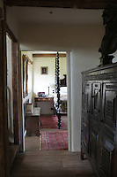 On the landing a carved antique bust is displayed on a massive carved chest with a view to the bedroom furnished with a large four-poster bed