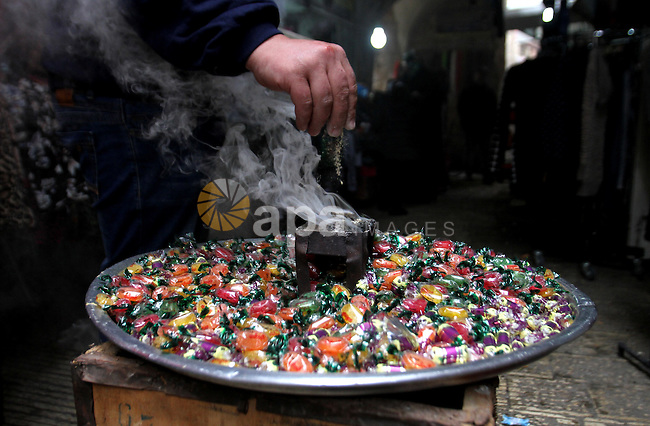 "Palestinians eat candy during a ritual ceremony to commemorate the birth of the Prophet Mohammed, known in Arabic as ""al-Mawlid al-Nabawi"", in the West Bank city of Nablus on December 11, 2016. Photo by Nedal Eshtayah"