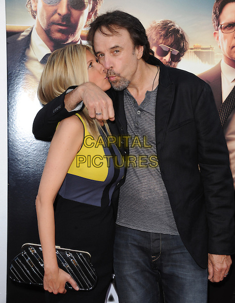 """Susan Yeagley & Kevin Nealon.""""The Hangover Part III"""" Los Angeles Premiere held at the Westwood Village Theater, Los Angeles, California, USA..May 20th, 2013.half length husband wife yellow blue dress clutch bag arm over shoulder kiss kissing profile funny married grey gray black goatee facial hair shirt.CAP/DVS.©DVS/Capital Pictures"""