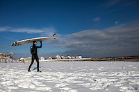 Mark Kielpinski, of Brewster, MA, walks across a snowy beach to go surfing at Green Harbor in Marshfield, MA, on a cold February day.