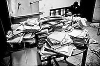 A hospital staff member tries to sort through patients files at the Rajan Babu TB hospital in New Delhi, India.