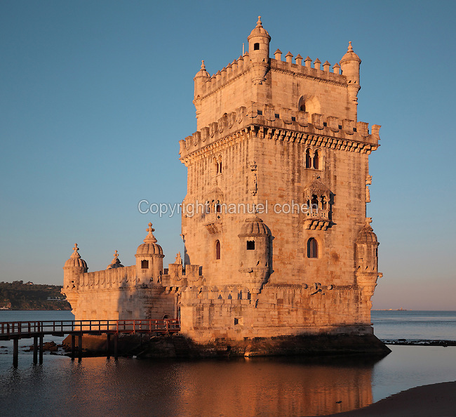 The Torre de Belem or Belem Tower, built in the 16th century by Francisco de Arruda under King John II as part of a defence system at the mouth of the river Tagus and a ceremonial gateway to the city, Santa Maria de Belem, Lisbon, Portugal. The limestone tower is built in Late Gothic Manueline style, and consists of a bastion terrace (left), 4 storey tower and small access bridge. It is listed as a UNESCO World Heritage Site due to its important role during the Portuguese Age of Discoveries. Picture by Manuel Cohen