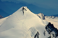 Aerial view of climbers approaching high snow-covered peak in the Swiss Alps