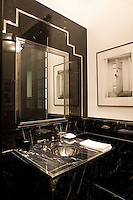 The black Marquina marble of an art-deco style guest bathroom is reflected in a chrome finished mirror in a Madrid apartment