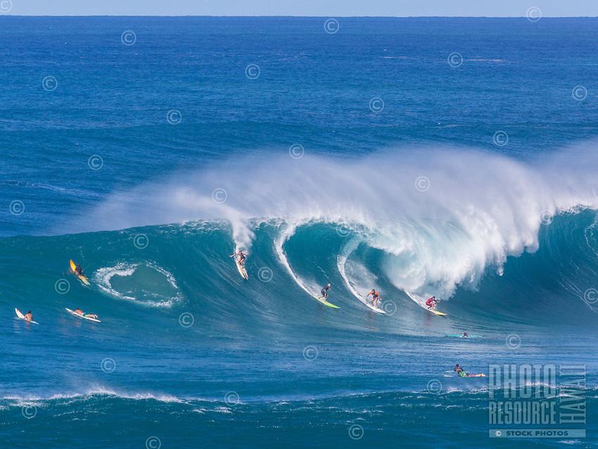 Four surfers - one woman and three men - drop into a huge wave at Waimea Bay, O'ahu.