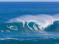 Four surfers - one woman and three men - drop into a huge wave at Waimea Bay, O'ahu.
