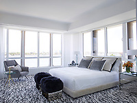 The luxurious penthouse apartment is light and spacious. In the master bedroom has a calming palette with a hint of shimmering blue. The room features stools by Azadeh Shladovsky from Jean de Merry, 1970s bedside tables by Karl Springer topped with lamps by Roberto Rida, and a 1960s Italian armchair; the Lucite headboard is a custom design, as is the rug by Beauvais Carpets.