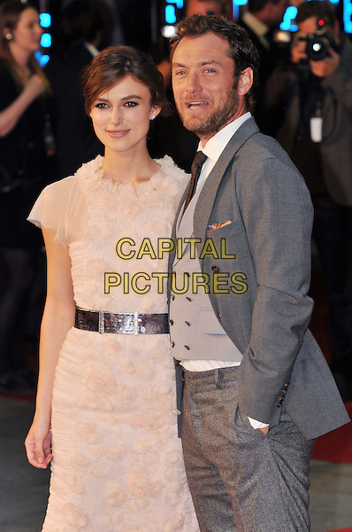 Keira Knightley (wearing Chanel) & Jude Law.The World Premiere of 'Anna Karenina', The Odeon Leicester Square, London, England..4th September 2012.half length peach pink white sheer fluffy ruffle dress silver belt grey gray suit waistcoat beard facial hair hand in pocket mouth open.CAP/BF.©Bob Fidgeon/Capital Pictures.