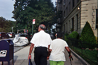 An elderly couple walks towards the subway on Eastern Parkway in the morning.