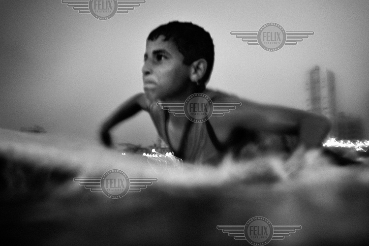 13 year old surfer Mahmoud Bakeat battles with the waves in the Mediterreanean Sea while paddling out from Gaza City.