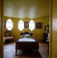 The golden yellow master bedroom is lit by three of the property's signature hexagonal-shaped windows