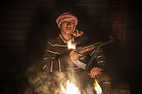 Hassan, a sixteen years old rebel fighter poses for photo as he holds his kalashnikov at a rebel base located in Tarik Al-Bab, a working class neighborhood fierce punished by heavy artillery and bombing and one of the rebel's stronghold of Aleppo, Syria.