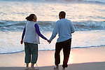 Mature couple holding hands at beach, rear view