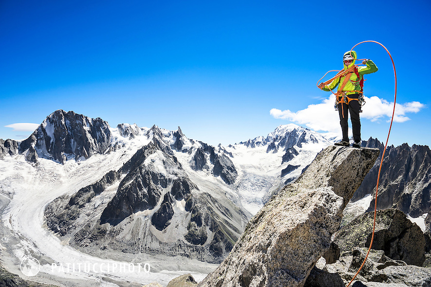 Climbing the Aiguille du Moine's South Ridge Integral, D. A long alpine rock ridge in Chamonix, France. The climber is coiling the rope on the summit.