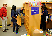 United States President Barack Obama (c) assists in putting in book shelves as he joins volunteers in a library as they participate in a service project, at Browne Education Center, in Washington, DC, USA, on the Martin Luther King Jr national holiday, 16 January 2012. The project was in memory of the legacy of community service, promoted by the late civil rights leader, who was assassinated in 1968.   .Credit: Mike Theiler / Pool via CNP