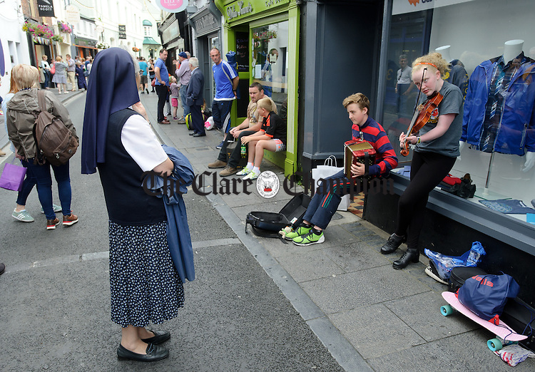A nun stops to listen to street performers during Fleadh Cheoil na hEireann in Ennis. Photograph by John Kelly.