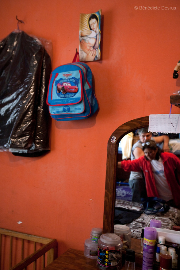 "April 26, 2009 - Mexico City, Mexico - Oscar's grandparents stand in his room in their apartment in Mexico City after receiving the boy's ashes. In the wall hangs Oscar's school bag. Oscar Corona Perez, 5 years old, died yesterday after 8 days of treatment at ""La Raza"" national medical center. The family was told on Friday that the medication and operations that had been done had no effect as Oscar had a new illness with no treatment. The next morning he died at 11:00 AM of pneumonia caused by swine Flu. The death toll has risen to over 80 people in Mexico City, and 929 people have the disease. All dead bodies with the influenza must be cremated. Photo credit: Benedicte Desrus / Sipa Press"