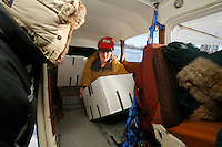 Volunteer pilot Diana Moroney loads her Cessna 185 at the Willow airport during the first day of flying straw, musher's dog food bags and people food & gear out to checkpoints south of the Alaska Range.  Saturday Feb. 21, 2009