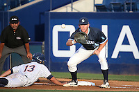 Tony Conyers (14) of the University of San Diego Toreros takes a pick off throw at first base as Timmy Richards (13) of the Cal State Fullerton Titans dives back to the bag during a game at Goodwin Field on April 5, 2016 in Fullerton, California. Cal State Fullerton defeated University of San Diego, 4-2. (Larry Goren/Four Seam Images)