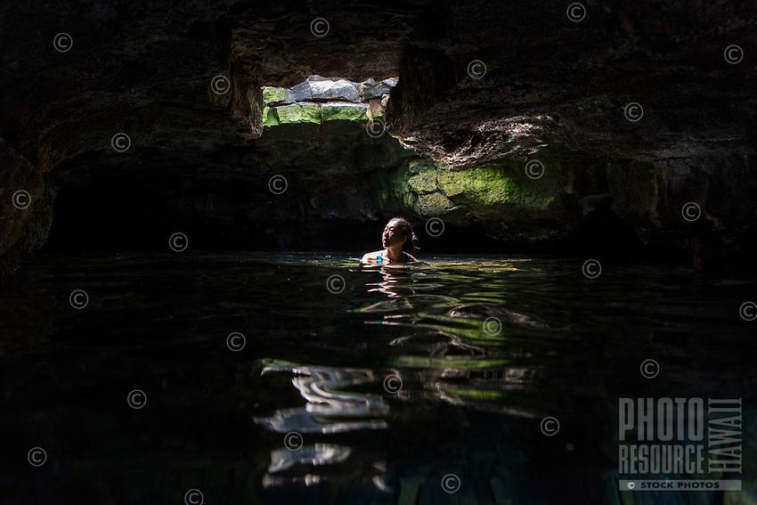 An Asian woman enjoys a fresh water cave at Queen's Bath at Kiholo Bay, Big Island.